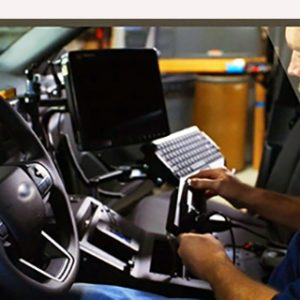 Employee servicing a radio inside an automobile
