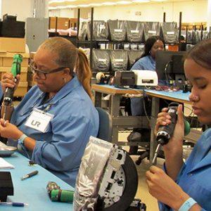 Employees soldering electronics