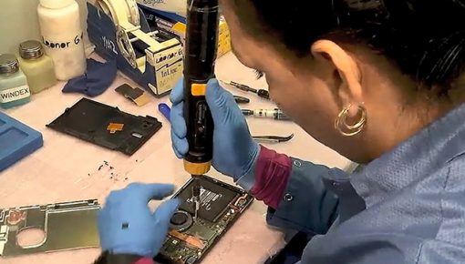 Employee performs soldering on consumer electronics